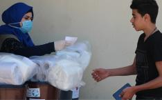 A woman wearing a facemask gives cleaning supplies and toilet paper to a young man