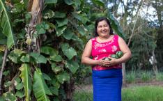Woman smiles and stands by fruit tree