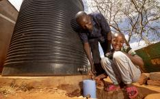Father stands with child by a well