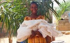 Woman smiles and holds mosquito net